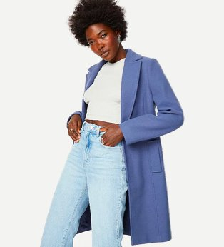 Woman poses with hands in pockets wearing white knitted crop top, light blue high-rise jeans and blue one button longline Crombie coat.