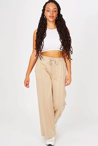 Woman walks towards camera wearing white crop top, cream wide leg pleated front elasticated joggers and white trainers.