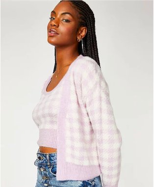 Woman poses side-on wearing lilac gingham knitted top and co-ord cardigan set and blue high-rise jeans.