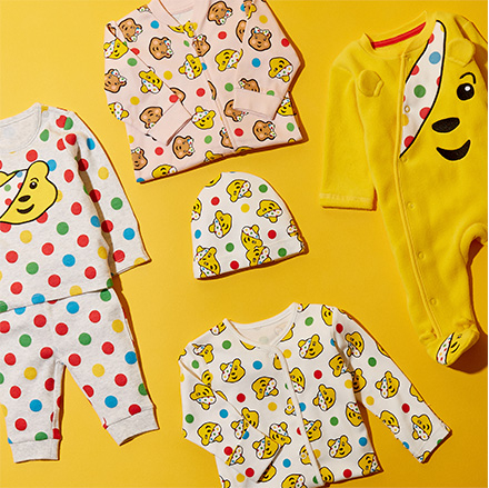 Bird's-eye view of Children in Need Pudsey Bear clothing, including a baby all in one and hat