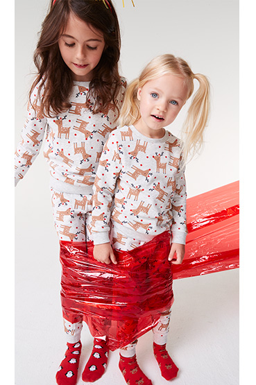Two girls wearing Christmas pyjamas wrapped up in red cellophane