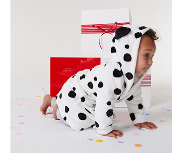 Baby crawling on the floor next to a stack of presents wearing a Dalmatian onesie