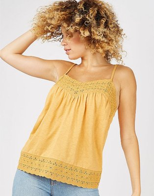 Woman poses with hand in hair wearing orange crochet trim vest top and light blue jeans.