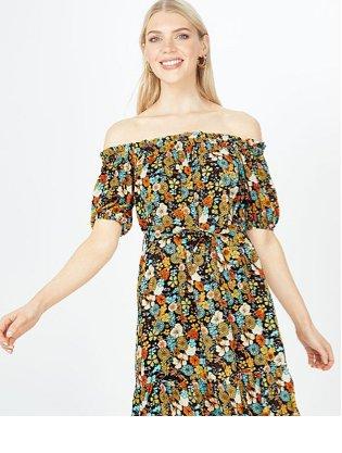 Woman poses smiling wearing floral print Bardot mini dress.