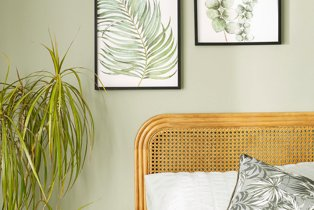 Room features leaf wall prints, double bed with wicker headboard and large artificial plant.