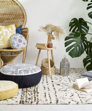 Room features wicker basket chair topped with blue and yellow printed cushions with wooden side table topped with giraffe vase, books and a candle with large artificial plant in corner of room.