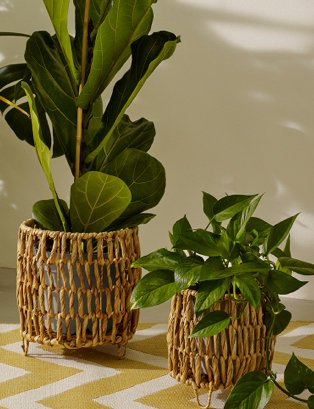 Set of 2 natural water hyacinth planters feature artificial plants.
