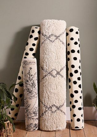 Assortment of abstract printed rugs stood upright on wooden floor against grey wall.