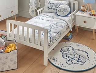 Bedroom features white bed topped with Disney Dumbo bedding, white side table, Disney Dumbo storage box and Disney Dumbo rug.