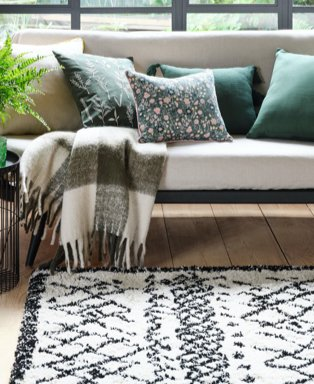 Room features cream sofa topped with green cushions, green checkered throw and homemaker black & white pattern Berber rug.