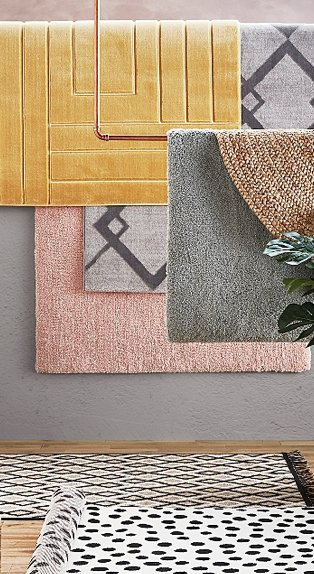 Mustard rug, grey diamond shimmer rug, pink rug, natural handspun jute rug layered together hanging over wooden floor featuring monochrome polka dot rug and natural flatweave printed rug.