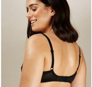 Reverse shot of woman looking down wearing black bra.
