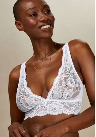 Woman poses smiling wearing white lace bralette.