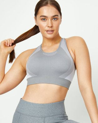 Woman poses holding end of ponytail wearing grey textured sports bra and leggings.