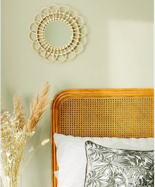 Shot of section of double bed with texured headboard, white and grey floral bedding with large artificial plant and rattan mirror in the background.
