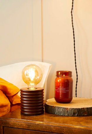 Wooden-effect bedside table features brown ribbed retro lamp and brown candle on tree bark-effect coaster.