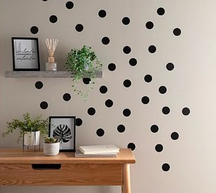 Room with polka dot patterned wall features wooden-effect desk topped with artificial plants, framed print and books, grey shelf features framed print, reed diffuser and artificial plant.