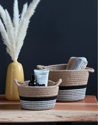 Wooden-effect table features two striped storage baskets and an artificial plant in yellow vase.