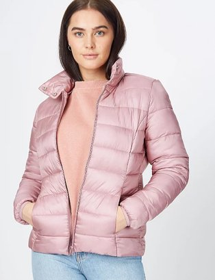 Woman in pink puffer jacket, pink top and jeans.