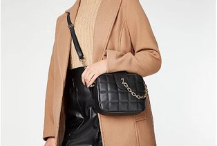 Woman in camel coat, with a camel top, black cross body bag and patent leather skirt.