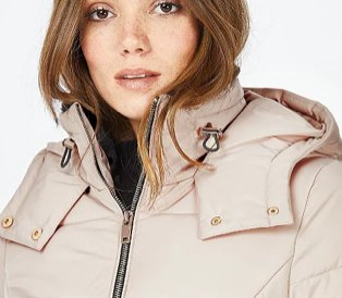 Woman in beige puffer jacket and black turtle neck top.