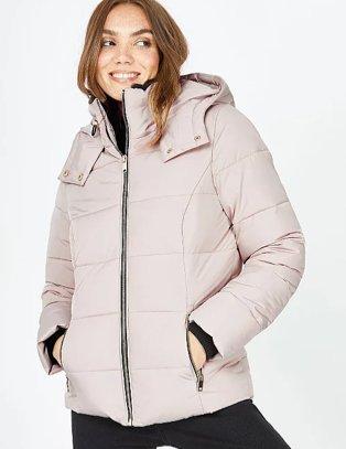 Woman in beige puffer jacket and black leggings.