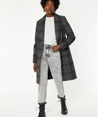 Woman in grey checked coat with white top, faded grey jeans and black military style boots.