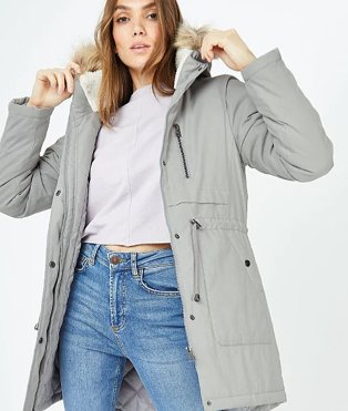 Woman in grey coat with fur trim hood white top and jeans.