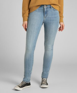 Woman in mustard jumper and faded denim jeans and canvas shoes.