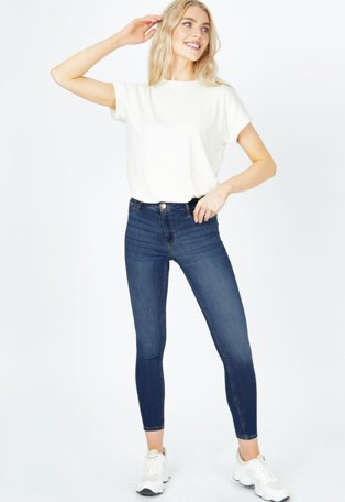 Woman wearing white t-shirt and denim jeans with white trainers.