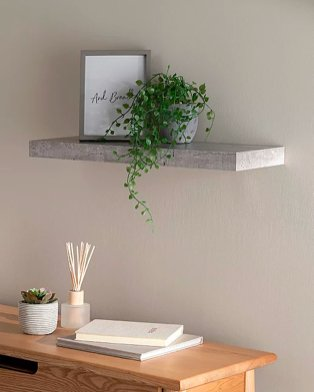 Grey room features shelf with framed print and artificial plant above wooden desk with books, reed diffuser and an artificial plant.