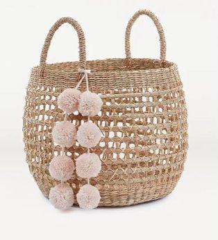 Brown rattan-effect storage basket with pink pom-pom detailing.