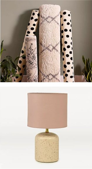 Assortment of abstract patterned rugs leaning against grey wall surrounded by artificial plants. Cream speckled table lamp with pink shade.