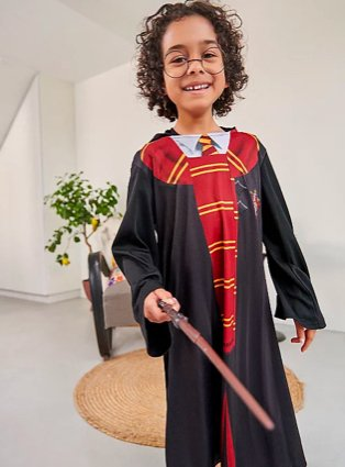 Young boy poses smiling wearing Harry Potter fancy dress outfit.