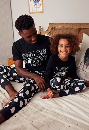 Smiling man and child huddle together on a bed wearing matching Halloween ghost slogan glow in the dark pyjamas set.