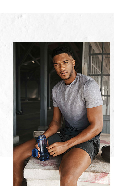 Theo Campbell sitting on a counter with a water bottle wearing a grey sports top and shorts
