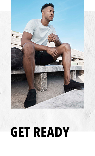 Theo Campbell sitting on a stone bench outdoors wearing a white sports top, black shorts and black trainers