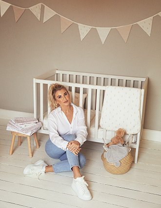 Billie Faiers sitting on the floor in front of a white wooden crib with baby bedding, toys and cushions surrounding her