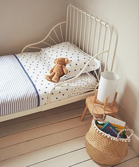 And a toddler bed with a white metal frame, white and blue bedding and a teddy on top, with a woven basket full of books on the floor