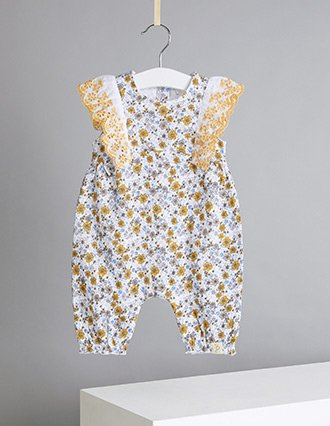 An ochre floral broderie anglaise trim romper hanging from a white hanger on a ribbon