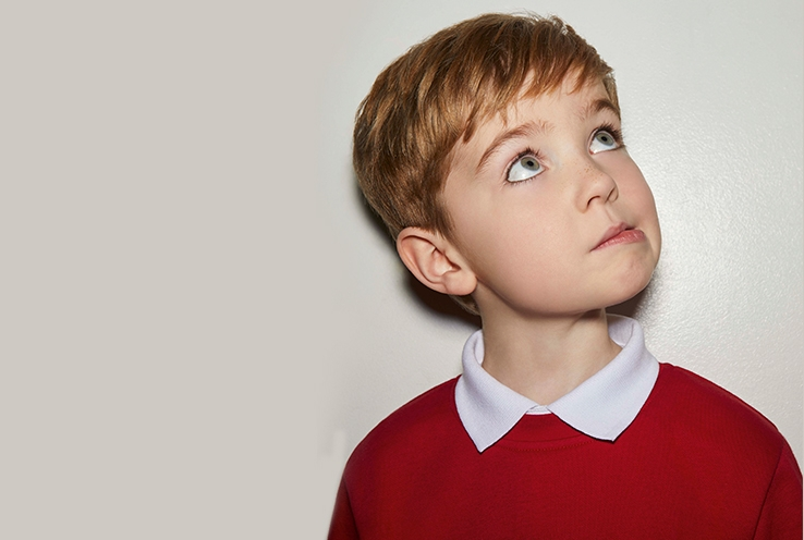 Boy looks up tilting head wearing white polo shirt and red school jumper.