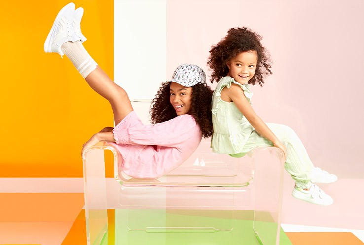 Two girls sit back to back, one wearing a pink dress with ruched sleeves, beige socks, white trainers and floral baseball cap next to another girl wearing lime green sleeveless frilly top and matching frilly detail trousers and white trainers.