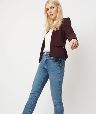 Woman wearing relaxed fit jeans with a white top and burgundy blazer