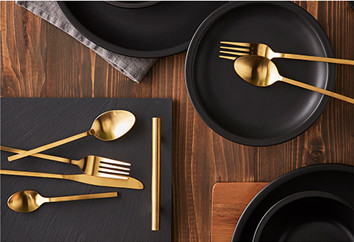 Black crockery and chopping board with gold cutlery