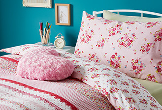 Bed with pink bedding and matching throws and a heart shaped cushion