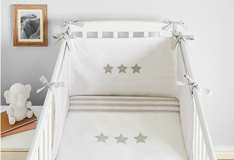 Image of nursery including a photo on the wall, elephant toy and a white cot with white star print bedding