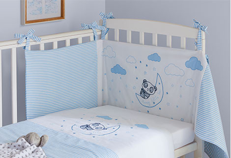 Image of nursery with white cot bed with blue and white bedding featuring a panda and clouds