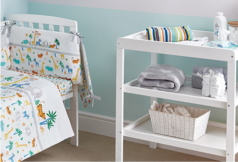 Image of nursery including a cot bed with white bedding featuring animals and a baby changing unit with accessories
