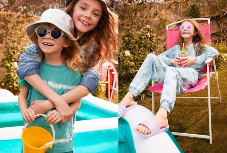 Two girls smile hugging in garden wearing brightly coloured clothes, sun hats and sunglasses. Girl smiles sitting on pink deck chair in garden holding drink wearing white and blue acid wash jumper and joggers, pink sunglasses and lilac sliders.