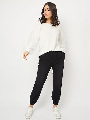 Woman in white long sleeve top, black bottoms and white trainers